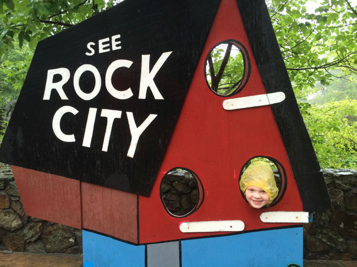 Girl looking through See Rock City sign