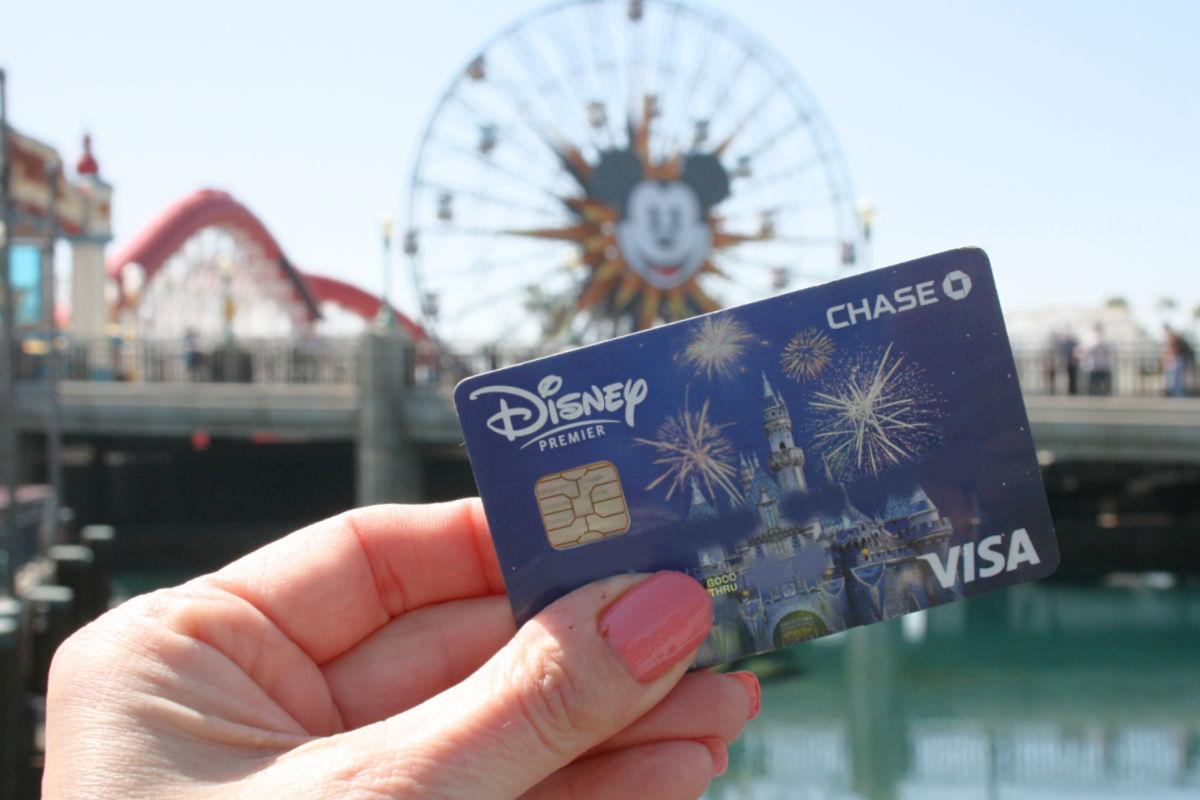 Disney credit card held up at Pixar Pier at Disney California Adventure park.