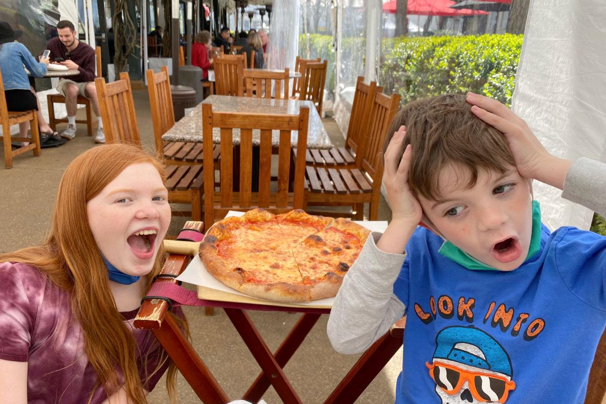 Kids enjoying pizza at Pizzeria Tra Vigne in St Helena in Napa Valley California