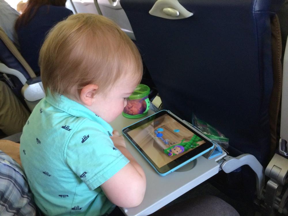 Toddler watching iPad on airplane.