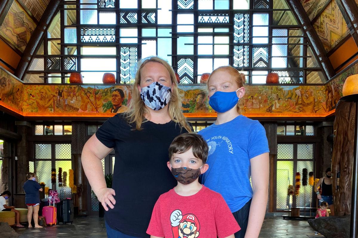 Family wearing masks in lobby of Disney's Aulani Resort.